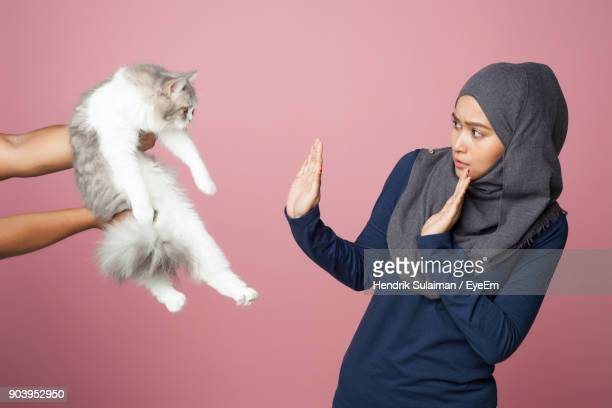 young woman with cat against pink background - menselijk lichaamsdeel stockfoto's en -beelden