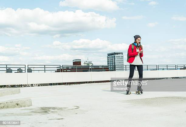 Young woman with cell phone and inline skates on parking level