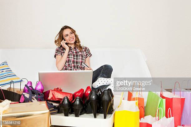 young woman with cell phone and laptop on couch surrounded by shopping bags and new shoes - surrounding stock pictures, royalty-free photos & images