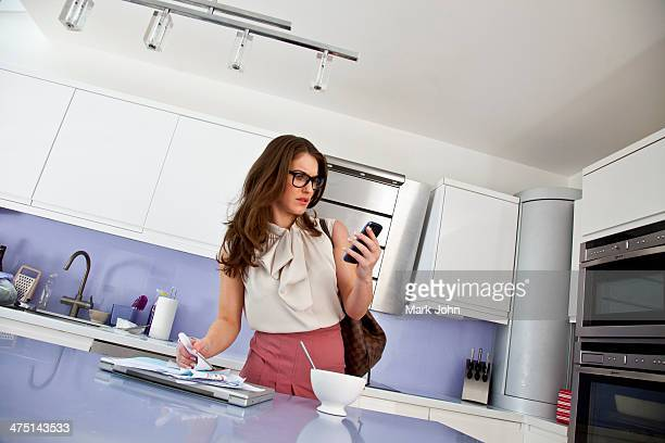 Young woman with cell phone and paperwork at breakfast