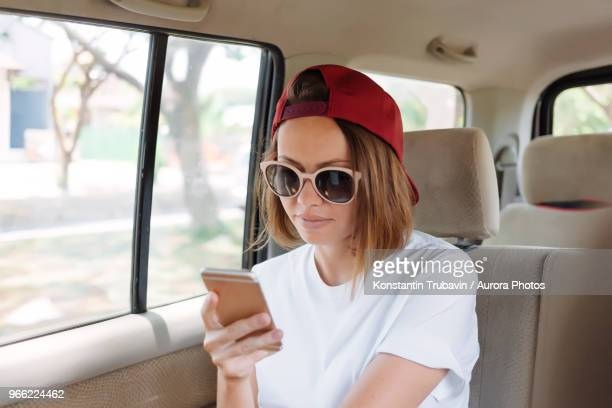 Young woman with  cell phone in car