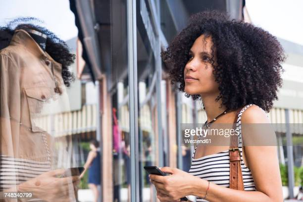 Young woman with cell phone looking in shop window