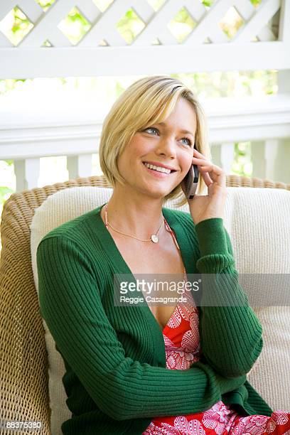 young woman with cell phone - mid adult woman sweater stock pictures, royalty-free photos & images