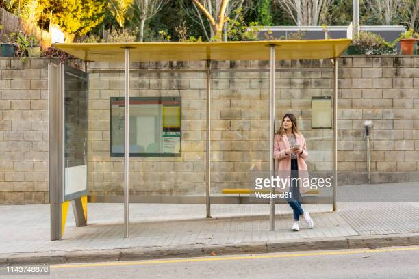 young woman with cell phone waiting at bus stop - waiting stock pictures, royalty-free photos & images