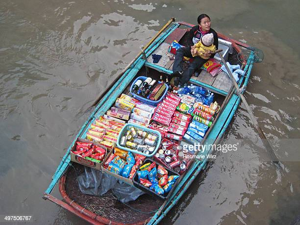 Young woman with child offering snacks and drinks on a boat. Ha Long Bay, Vietnam.