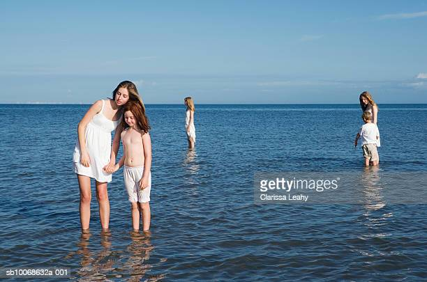 Young woman with children (8-17) standing in sea