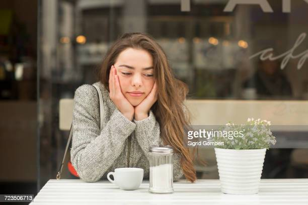 young woman with chin in hands at sidewalk cafe - sigrid gombert stock pictures, royalty-free photos & images