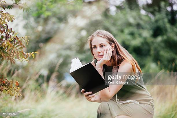 Young woman with chin on hand reading book in field