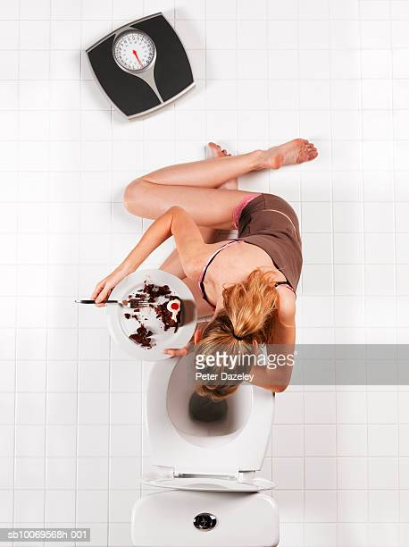 young woman with chocolate cake vomiting into toilet bowl, directly above - bulimia fotografías e imágenes de stock