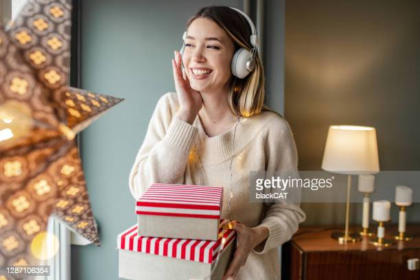 young woman with christmas presents at home - christmas music stock pictures, royalty-free photos & images