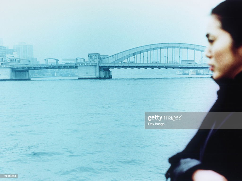 Young woman with city in background, close up : Stock Photo
