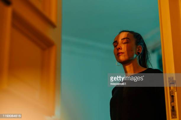young woman with closed eyes in shadow and light at open door - in den zwanzigern stock-fotos und bilder