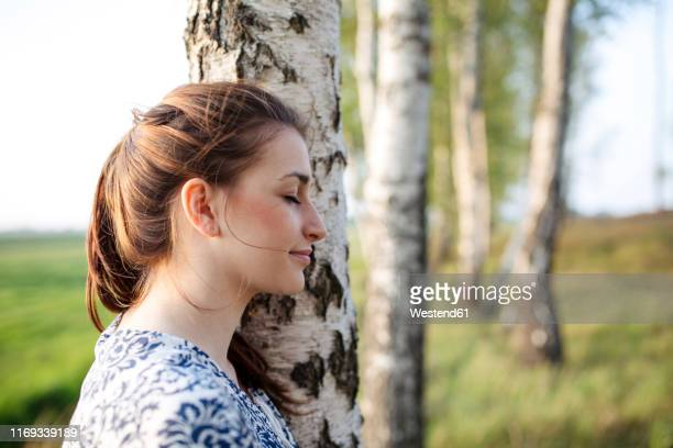 young woman with closed eyes leaning on a tree trunk enjoying nature - sinneswahrnehmung stock-fotos und bilder