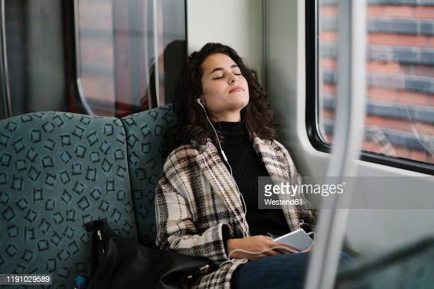 young woman with closed eyes relaxing on a subway - subway train stock pictures, royalty-free photos & images