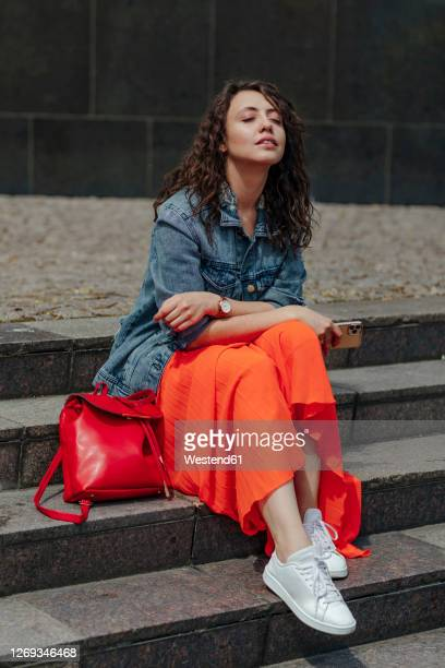 young woman with closed eyes sitting on stairs enjoying the sun - jacket stock pictures, royalty-free photos & images