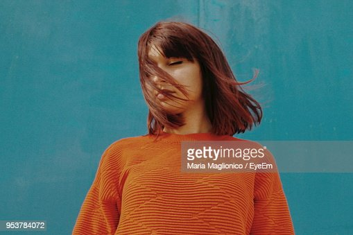 Young Woman With Closed Eyes Standing Against Blue Wall