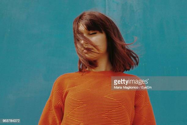young woman with closed eyes standing against blue wall - redhead stock pictures, royalty-free photos & images