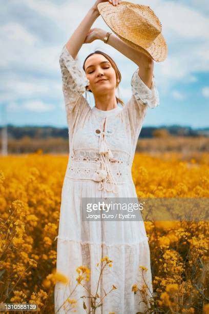 young woman with closed eyes standing on field against sky - leiria photos et images de collection