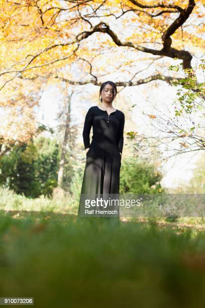 Young woman with closed eyes standing on field against trees at park