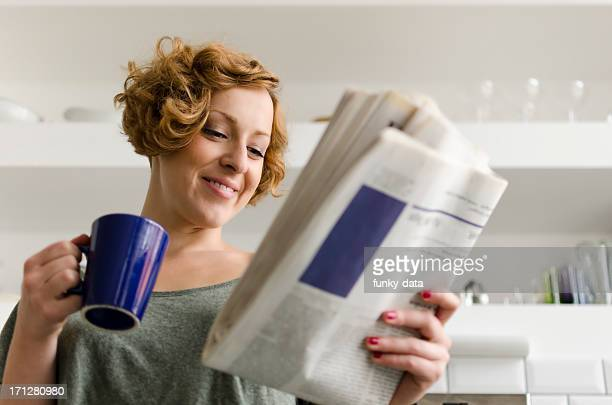Young woman with coffee and newspaper