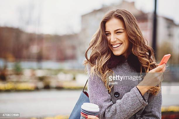 Young woman with coffee cup and phone smiling outdoors