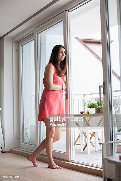 Young woman with coffee cup looking through window