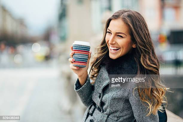 young woman with coffee cup smiling outdoors - bruin haar stockfoto's en -beelden