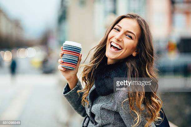 young woman with coffee cup smiling outdoors - pretty girls stock photos and pictures