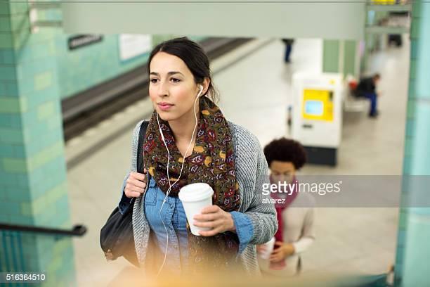 Jeune femme avec une tasse de café en sortant de la station de métro