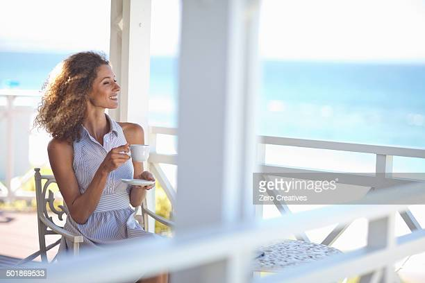 Young woman with coffee gazing out to sea from beach house balcony