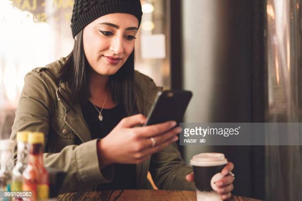 Young woman with coffee in her hand checking smartphone.
