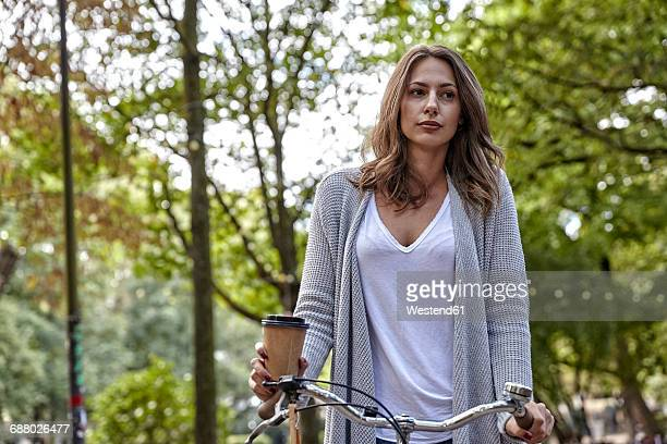 Young woman with coffee to go and bicycle