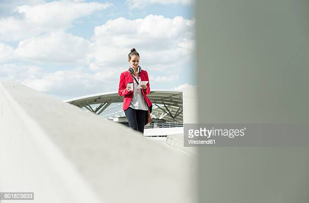 Young woman with coffee to go, headphones and phablet on parking level