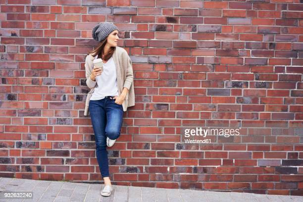 Young woman with coffee to go leaning at brick wall