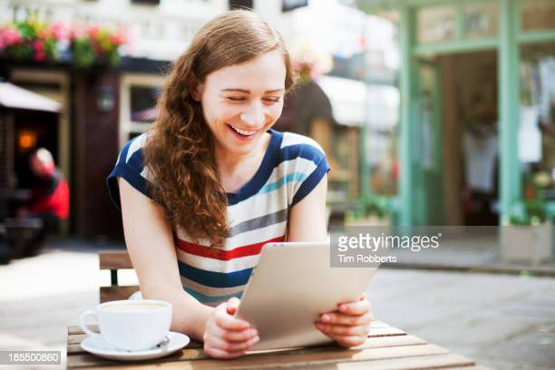 Young woman with coffee using digital tablet