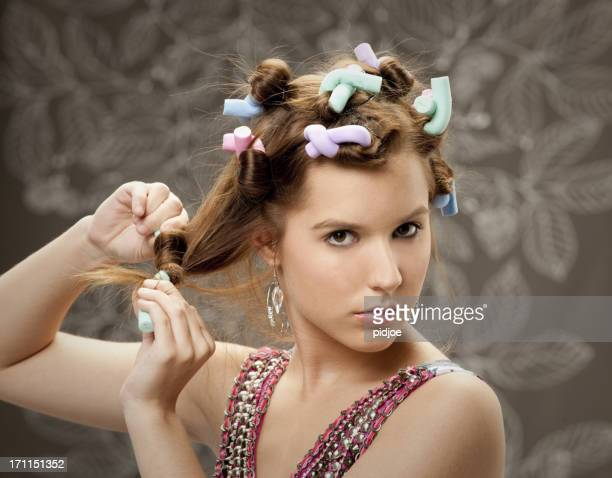 young woman with colorful curlers in hair