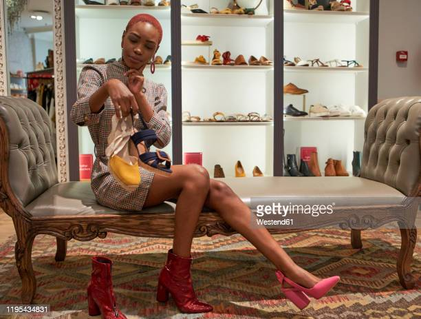 young woman with colorful haircut choosing the new pair of shoes to buy at a clothes shop - zwarte schoen stockfoto's en -beelden
