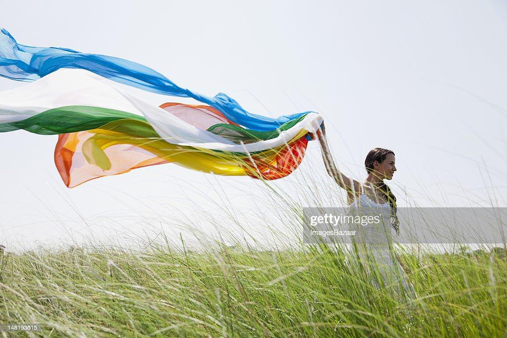 Young woman with colorful scarf walking on grass : Stock Photo