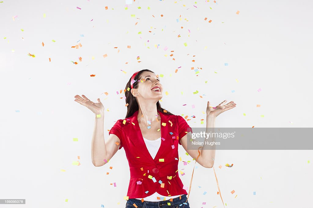 young woman with confetti falling around her : Stock Photo