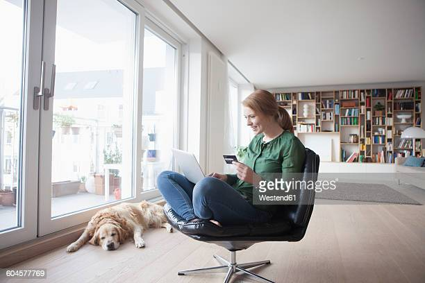 Young woman with credit card and laptop sitting on a leather armchair in her living room