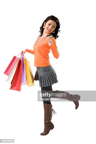 Young woman with credit card holding shopping bags