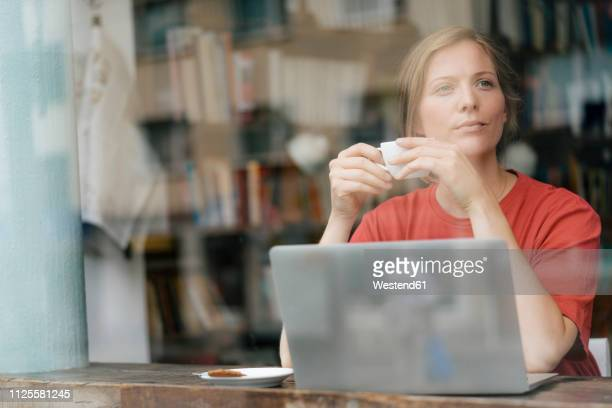 young woman with cup of coffee and laptop in a cafe - achter stockfoto's en -beelden
