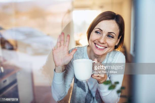 a young woman with cup of coffee looking out of a window, waving goodbye - winken stock-fotos und bilder