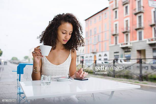 Young woman with cup of coffee using her smartphone