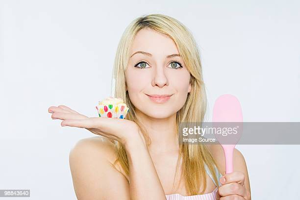 Young woman with cupcake and spoon