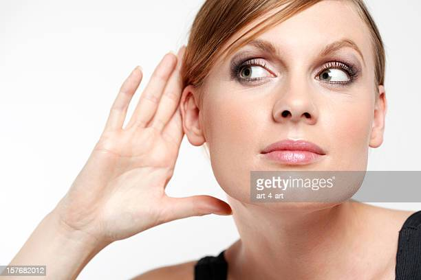 Young woman with cupping hand behind ear and eavesdropping
