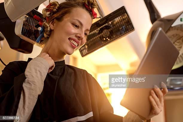 Jeune femme avec Bigoudi au salon de coiffure est à l'aide de tablette numérique.