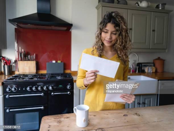 mujer joven con el pelo rizado bebiendo té y revisando su correo - e mail fotografías e imágenes de stock