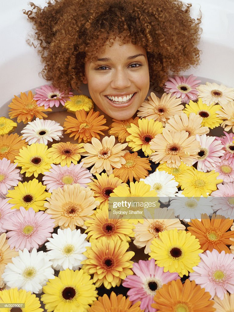 Young Woman With Curly Hair Lies in a Bath of Multicolored, Floating Flowers : Stock Photo
