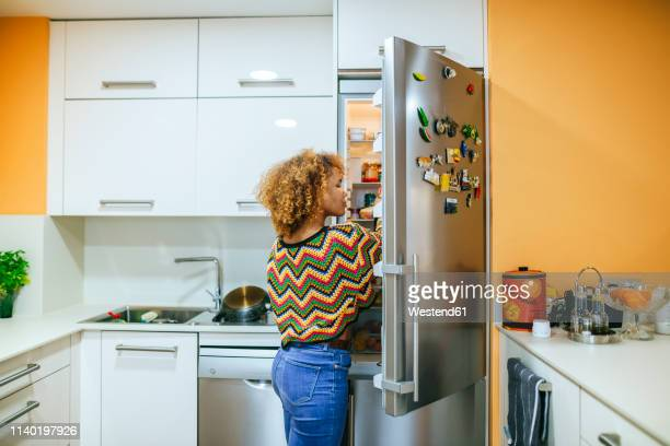 young woman with curly hair opening the fridge in kitchen - refrigerator stock pictures, royalty-free photos & images